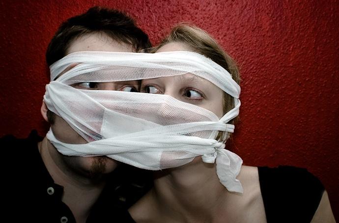 Zwei Jugendliche stecken die Köpfe zusammen und haben einen gemeinsamen Verband um den Kopf.
